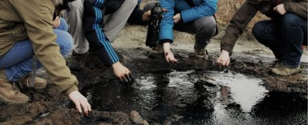 """Group of students at an """"oil seep"""" in the Ukraine. Surface shows of oil and gas are very common naturally-occurring phenomena."""